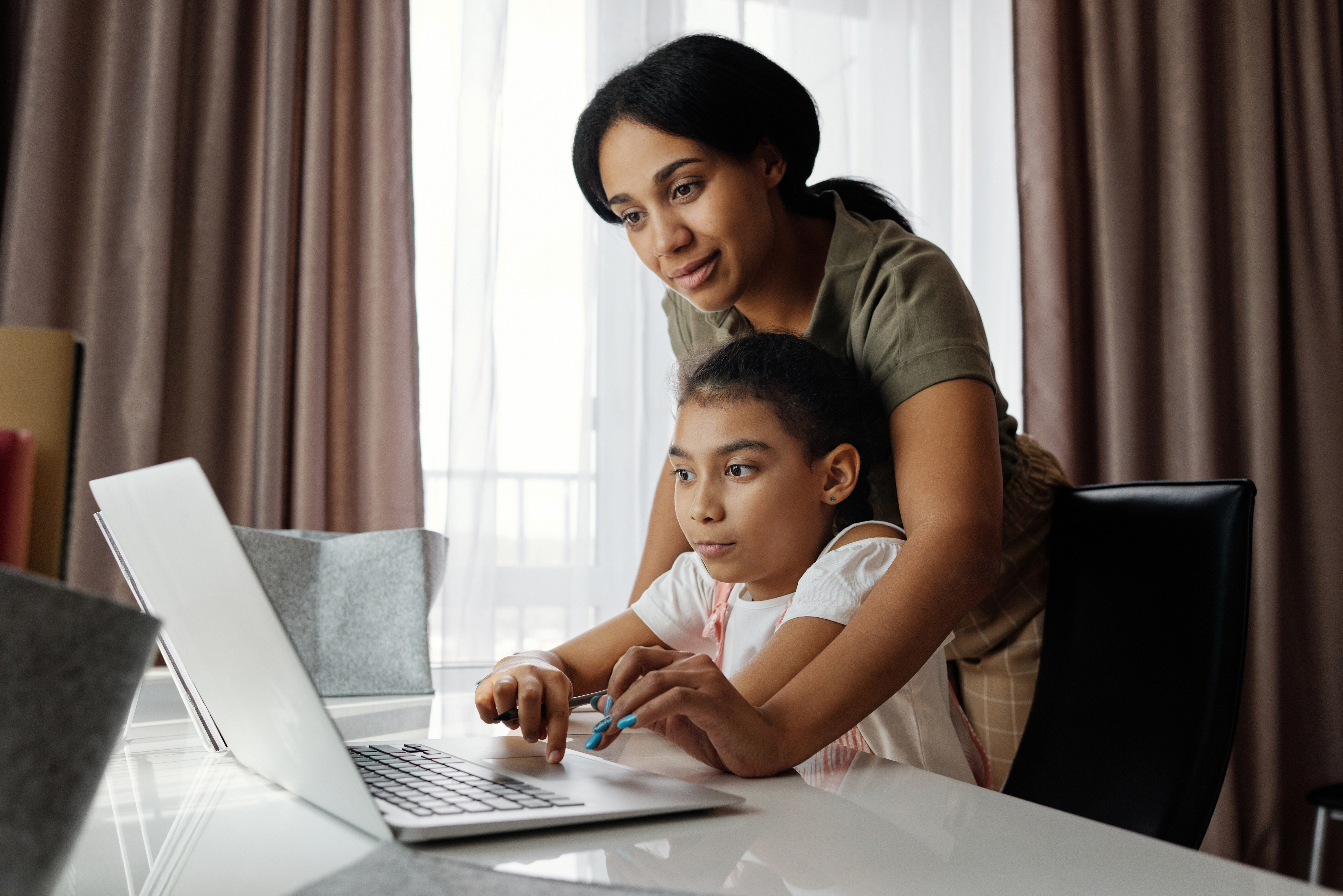 mother-helping-her-daughter-use-a-laptop-4260325